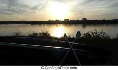 A catamaran looking boat with paddles on a lake bank at sunset