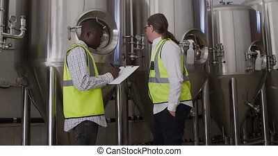 Caucasian and African American man working in a microbrewery...