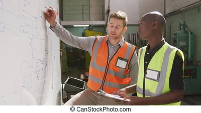 A Caucasian and an African American male factory worker ...