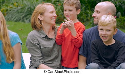 A caucasian family of five smile and listen to their youngest child talk- slowmo