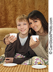 A Caucasian mother with her son sitting on the couch
