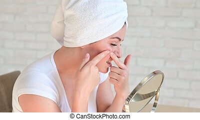 A Caucasian woman with a white terry towel on her head looks...