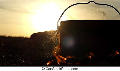 A cauldron with water stands in a bonfire at sunset in slo-mo
