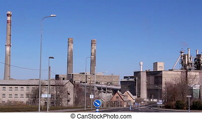 A cement factory with huge buildings inside it a red car is...