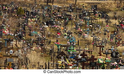 A cemetery filled with flowers and photos - A wide shot of a...