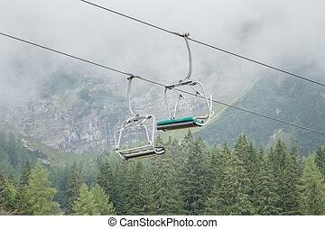 A chairlift with mountains in the background