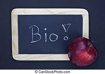a chalkboard with the message bio and an apple
