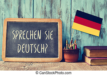 a chalkboard with the question sprechen sie deutsch? do you speak german? written in german, a pot with pencils, some books and the flag of Germany, on a wooden desk
