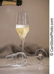 A champagne glass being filled with a lying down empty glass on an out of focus background