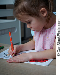A charming 4-year-old girl painstakingly paints a drawing of a flower in coloring with an orange pencil at a wooden table in her room at home