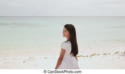 A charming and happy philippine teen girl in a white summer dress barefoot on a tropical beach by the ocean. Childhood. Recreation.