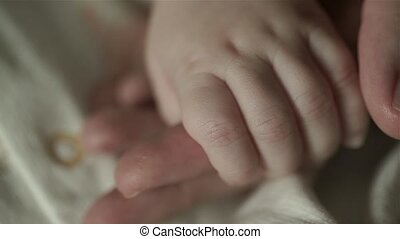 A charming baby is holding mother's finger. Mom stroked his hand with his thumb