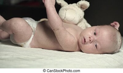 A charming baby lies on a bed with a plush toy and actively moves his arms
