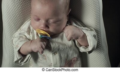 A charming baby with pacifier in his mouth sleeping on the bed.