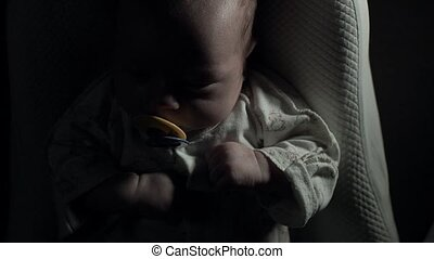 A charming baby with pacifier in his mouth sleeps on the bed.