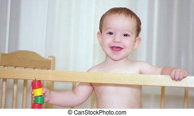 A charming child in a crib laughs and claps her hands and at the same time tries to make her mother laugh.