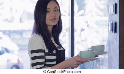 A charming female barista bring coffee