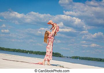 A charming girl in a light summer sundress walks on the sandy beach with her little daughter. Enjoys warm sunny summer days