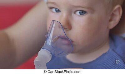 A charming little child in the mask of an inhaler. Procedure of inhalation. Treatment of lung diseases at home.