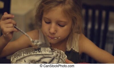 A charming little girl greedily eats the cream left in the kitchen after making the cake
