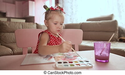 A charming little girl in a red dress paints with watercolor at the table.