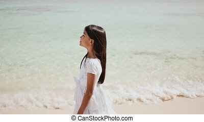 A charming philippine schoolgirl in a white dress is walking along a white sandy beach. Enjoying the tropical scenery. Childhood.