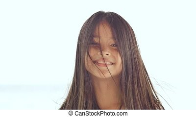 A charming philippine schoolgirl joyfully poses, rotating her hair. Face close-up on a white background of summer nature.
