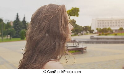 A charming sensual young girl in a summer dress is walking along the park in the center of the city. Her long hair flies in the wind. Enjoying a summer's day. The youth. Beauty.