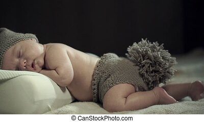 A charming sleeping baby in knitted cap with ears and shorts with a tail.