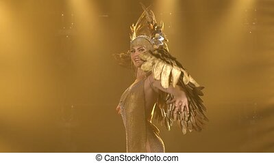 A charming woman actress in the image of the Greek goddess Artemis with golden wings sings and dances on stage. Theatrical vocal dance show. Close up