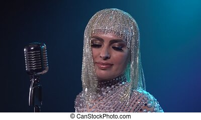 A charming woman in a chic shiny headdress and costume in rhinestones dances and sings into a vintage microphone against a background of blue light. Close up.