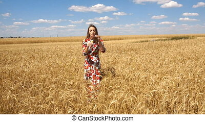 woman in dress standing in a wheat field and inflates soap-bubbles in slow motion