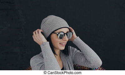 A charming young brunette girl wearing a gray hat and sunglasses listens to music in the headphones and sings, on a black background