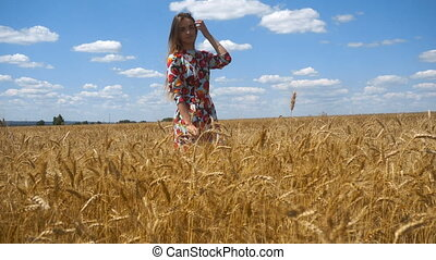 a charming young girl in a wheat field looks in the camera corrects hair