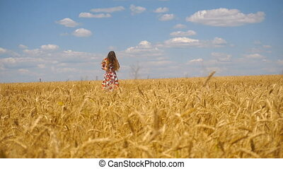 young girl standing in a wheat field hands straightens hair and smiles