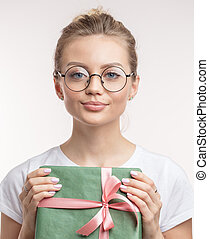 a charming young woman with Christmas gift looking at the camera