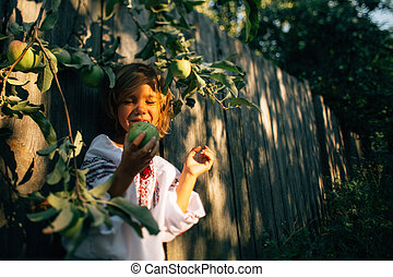 A cheerful and beautiful little girl in embroidered eating an apple