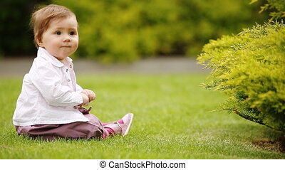 A cheerful baby-girl is sitting on the green grass near the bush in the city park.