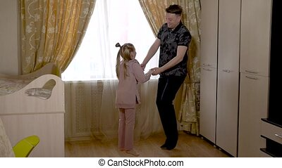 A cheerful best dad is dancing with a cheerful kid lighter in a large living room in fashionable clothes. On against a bright window.