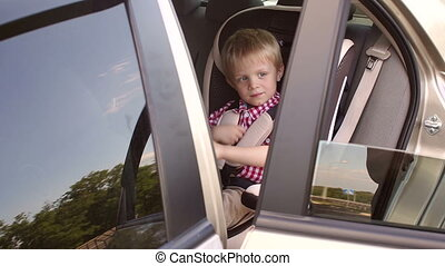 A cheerful boy of five years in a red shirt sits in a car seat and plays.