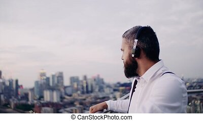 A cheerful businessman with headphones standing against...