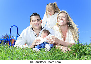 A Cheerful family lay in grass of a playground