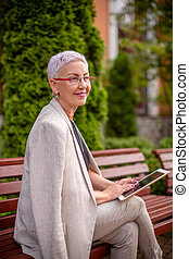 cheerful grandma is learing to use the tanblet outdoors - a ...
