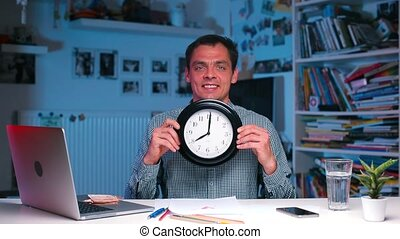A cheerful guy holds a watch in his hands on a watch at 08 00 hours.