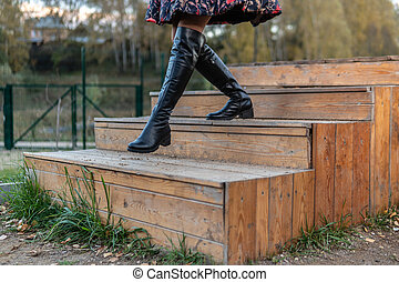 A cheerful lady walks up the stairs in a burgundy palette and biret, with a beautiful smile in black clothes, in the fall against a blue sky.