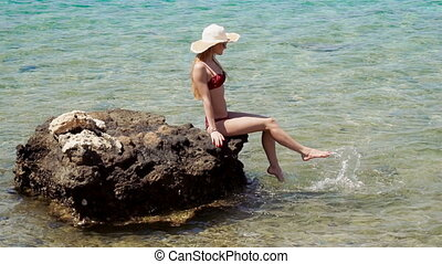 a cheerful young girl in a bathing suit and hat sits on a rock in the sea