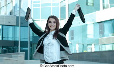 a cheerful young girl jumping and rejoices at the camera