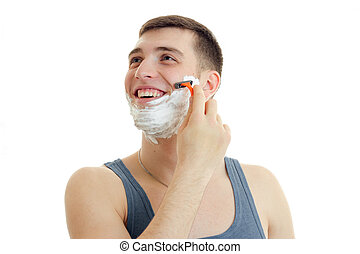 a cheerful young man with foam on his face looks toward the machine and shaves his beard