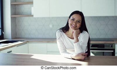 A cheerful young woman leaning on kitchen counter in new home, resting.