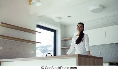 A cheerful young woman leaning on kitchen counter in new...